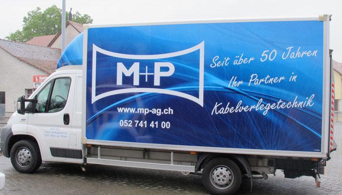 M+P Lieferwagen mit Festaufbau beschriftet durch Werbetafel